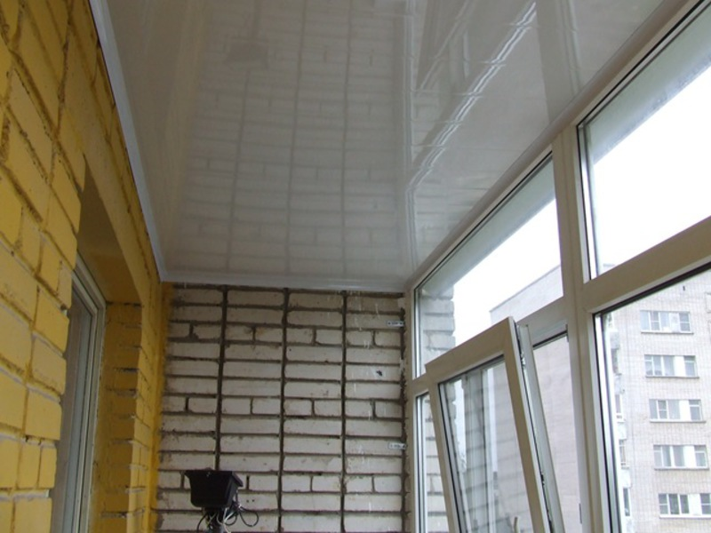 Отделка потолка на балконе белыми пластиковыми панелями..